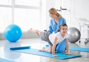 Physiotherapist working with little girl in rehabilitation center